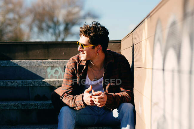 Young handsome guy in casual clothes looking away while sitting on stairs on sunny day on city street — Stock Photo