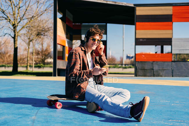 Happy hipster in casual clothes smiling and browsing smartphone while sitting on skateboard and listening to music on sports ground — Stock Photo