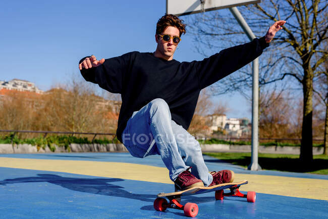 Young handsome male with raised arms falling from skateboard while trying to do trick on sunny day on sports ground — Stock Photo