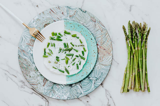 From above yummy white egg omelet with asparagus served on plate near fork and raw green asparagus on modern marble tabletop - foto de stock