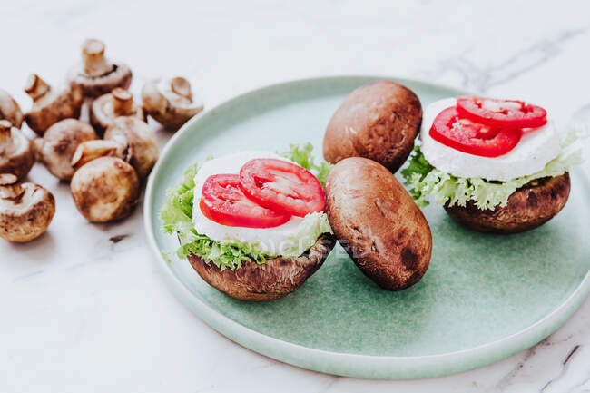 High angle of healthy bowls with mushrooms stuffed with lettuce and cheese with tomato slices served on green plate — стоковое фото