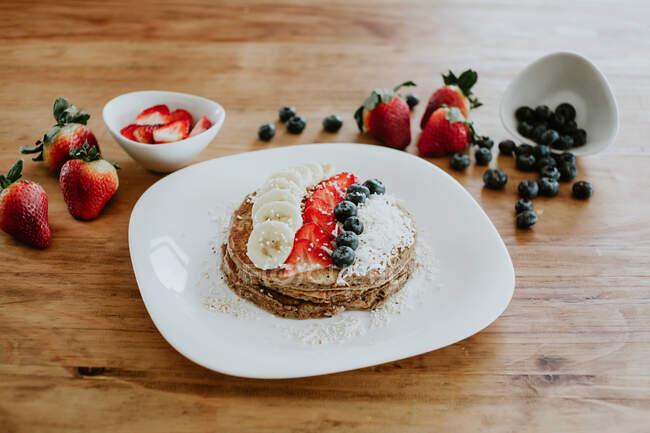 Pilha de panquecas saborosas servidas em prato com pedaços de banana e morango e mirtilos frescos com flocos de coco durante o café da manhã — Fotografia de Stock