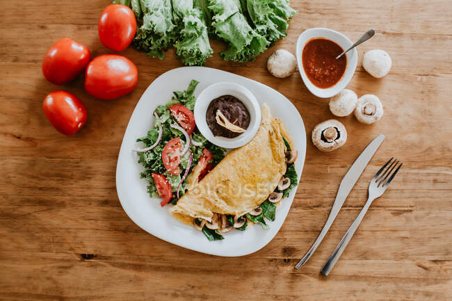 Vista superior del plato con taco de champiñones vegetarianos y ensalada de verduras saludables colocada sobre una mesa de madera cerca de tomates maduros con lechuga y salsa - foto de stock