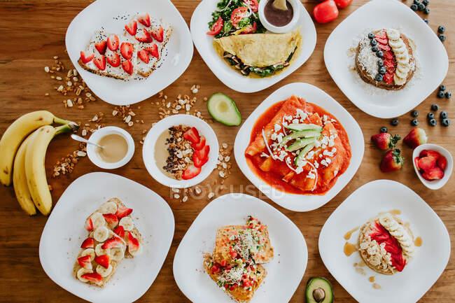 Vista superior de una variedad de platos veganos mexicanos y granola colocada en la mesa de madera en medio de plátanos maduros con aguacate y fresas con arándanos - foto de stock