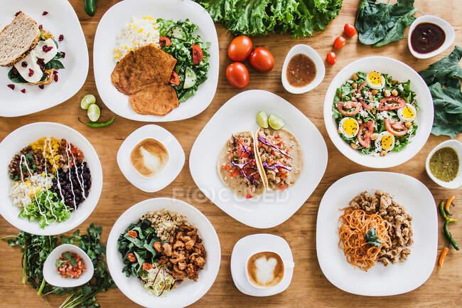 Tazones y platos de deliciosos platos saludables con verduras y carne colocados cerca de tazas de café y salsas con tomates y hierbas en la mesa - foto de stock