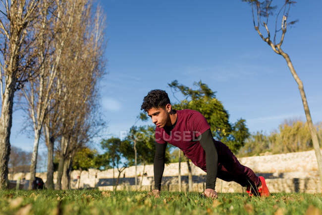 Young Hispanic male in sportswear doing push ups on green grass during fitness workout on sunny day in park — Stock Photo