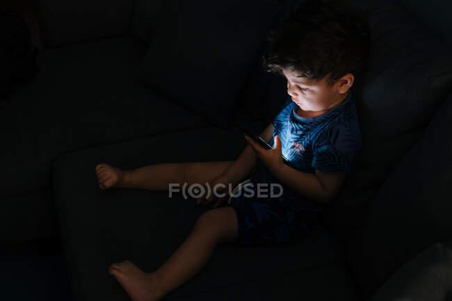 Любопытный маленький мальчик просматривает смартфон дома — стоковое фото