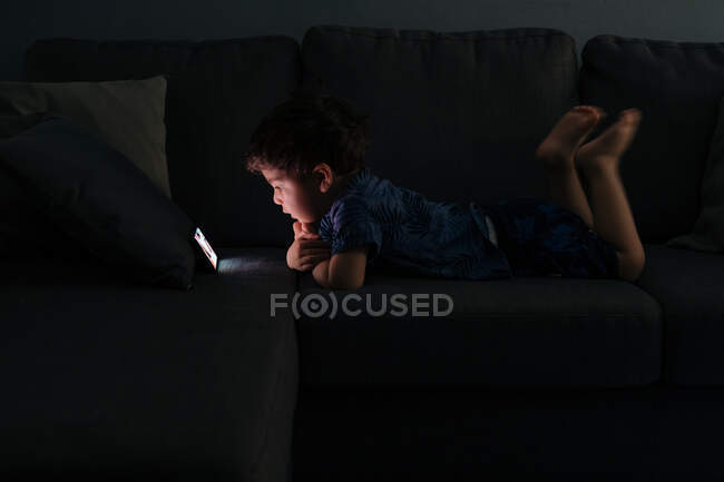 Curious little boy browsing smartphone at home — Stock Photo