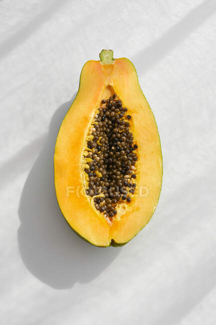 Top view of half of fresh healthy papaya with seeds placed on white table — Stock Photo