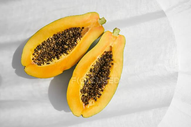 Верхній вид на половинки свіжої здорової папаї з насінинами на білому столі. — стокове фото