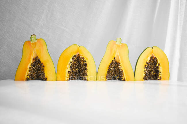 Pieces of fresh papaya with seeds placed on white background — Stock Photo