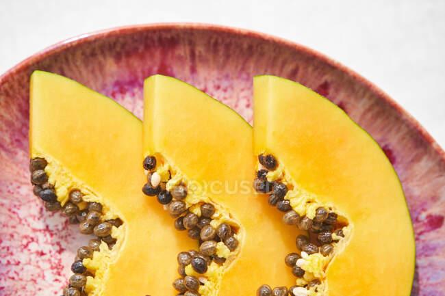 Dall'alto pezzi di papaia fresca con semi posti su piatto su sfondo bianco — Foto stock