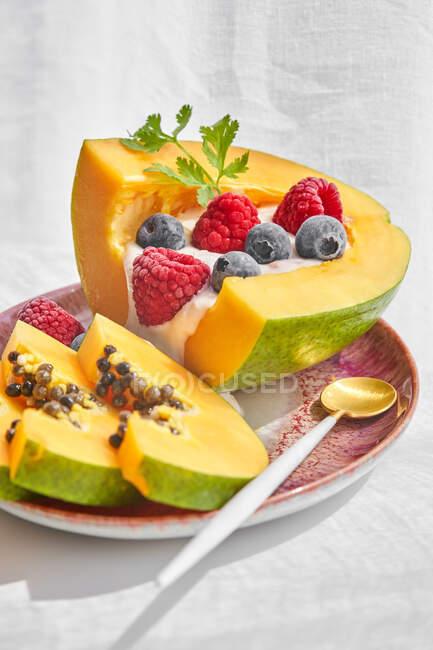 Сверху куски спелой папайи с йогуртом и свежими ягодами помещены возле ложки на тарелке на белом фоне — стоковое фото