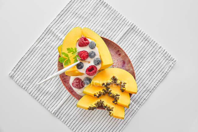 From above pieces of ripe papaya with yoghurt and fresh berries placed near spoon on plate on white background — Stock Photo