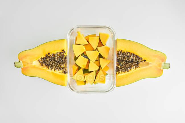 Vista dall'alto di metà papaia matura e contenitore di vetro con pezzi di frutta fresca posti su sfondo bianco — Foto stock