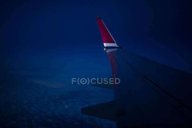 Através da visão da janela da asa do avião moderno voando sobre as nuvens na noite escura — Fotografia de Stock