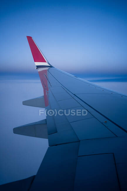 Through window view of wing of modern airplane flying over clouds in dark night time — Stock Photo