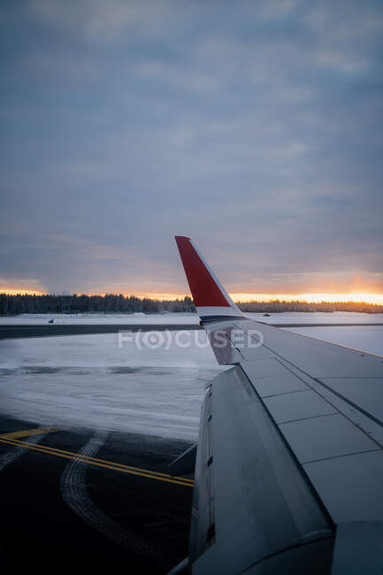 Wing of modern airplane on snowy terrain against dark forest at horizon and aircraft taking off from runway to gray sky in overcast weather at dusk in Norway — Stock Photo