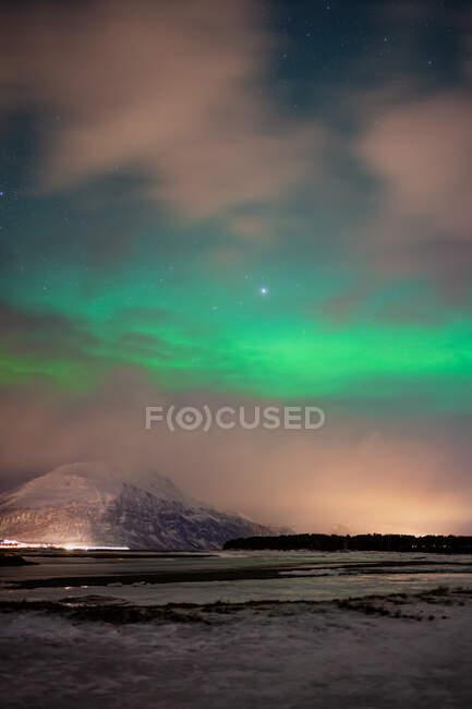 Paesaggio pittoresco con insediamento illuminato sulla riva dello stretto ai piedi di montagne innevate sotto cielo stellato nuvoloso con incredibili aurore boreali verdi a Lofoten — Foto stock