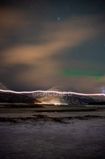 Picturesque scenery with illuminated settlement on strait shore at foot of snowy mountains under cloudy starry sky with amazing green Northern Lights in Lofoten — Stock Photo