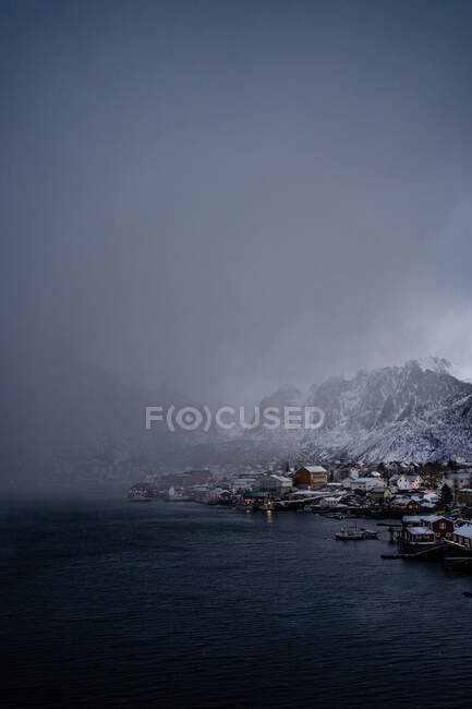 From above of city harbor against snowy mountain ridges at horizon in overcast weather in Norway — Stock Photo