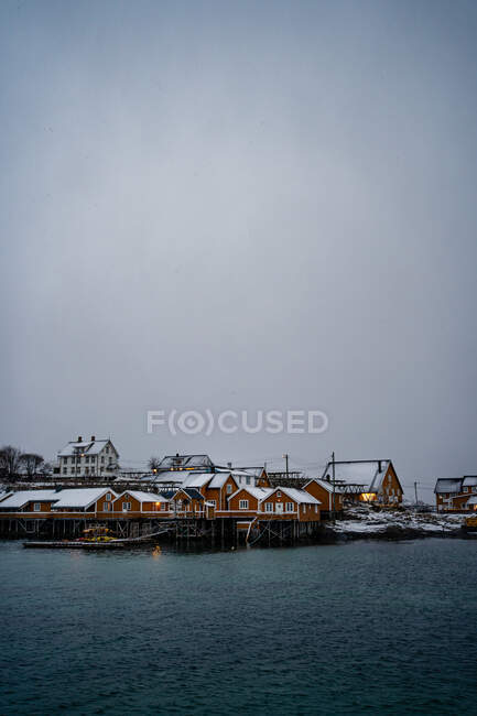 Snowy orange country houses on coast of strait with rippled water in cold overcast weather in Lofoten — Stock Photo