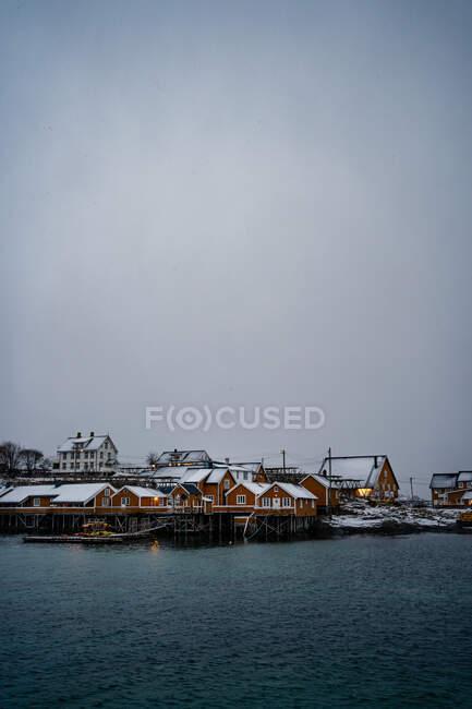 Case di campagna arancione nevoso sulla costa dello stretto con acqua increspata nel tempo freddo coperto in Lofoten — Foto stock
