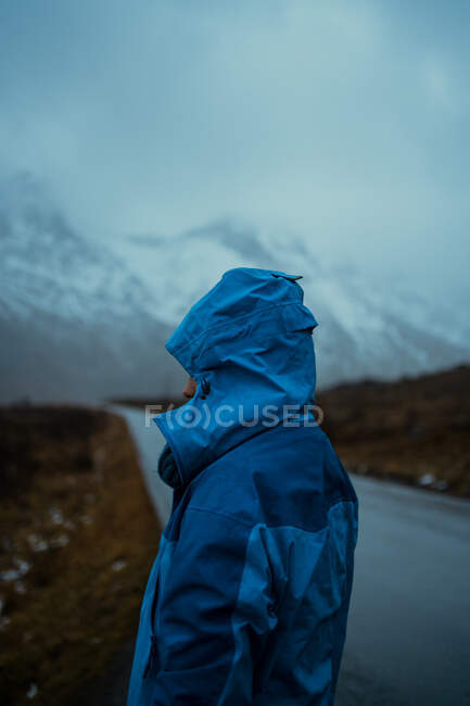 Back view of relaxed unrecognizable person in blue warm clothes and hoodie standing on asphalt road going to snowy foggy mountains in Lofoten — Stock Photo
