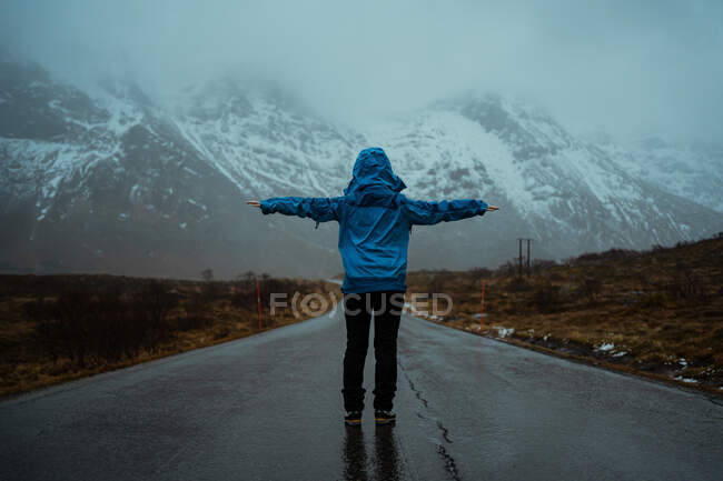 Back view of faceless woman in blue warm clothes enjoying idyll and freshness while standing with arms outstretched on asphalt road going to snowy foggy mountain ranges in Norway — Stock Photo