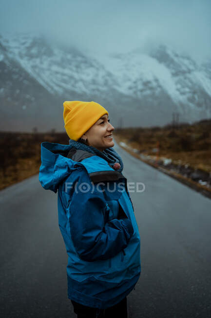 Side view of happy relaxed woman in blue warm clothes and bright yellow hat enjoying life while standing looking away on asphalt road going to snowy foggy mountains in Lofoten — Stock Photo