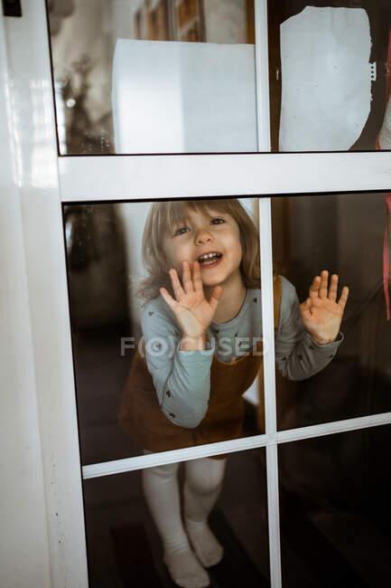 Petite fille mignonne en vêtements décontractés regardant la caméra et souriant tout en se tenant derrière la fenêtre à la maison et touchant le verre — Photo de stock