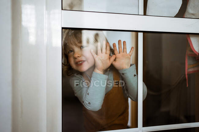 Cute little girl in casual clothes looking at camera and smiling while standing behind window at home and touching glass — Stock Photo