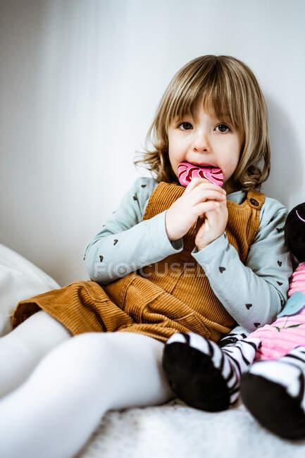 Carino bambina in abiti casual guardando la fotocamera e succhiare lecca-lecca mentre seduto sul comodo letto vicino giocattolo a casa — Foto stock