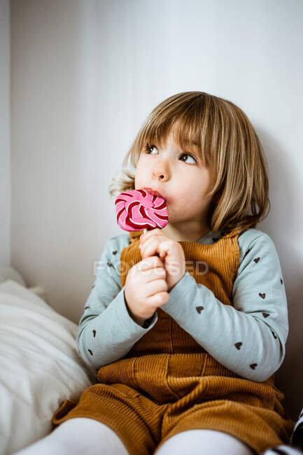 Cute little girl in casual clothes looking at camera and sucking lollipop while sitting on comfortable bed near toy at home — Stock Photo