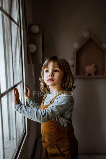 Adorable niña en ropa casual mirando por la ventana mientras descansa en la acogedora habitación en casa - foto de stock