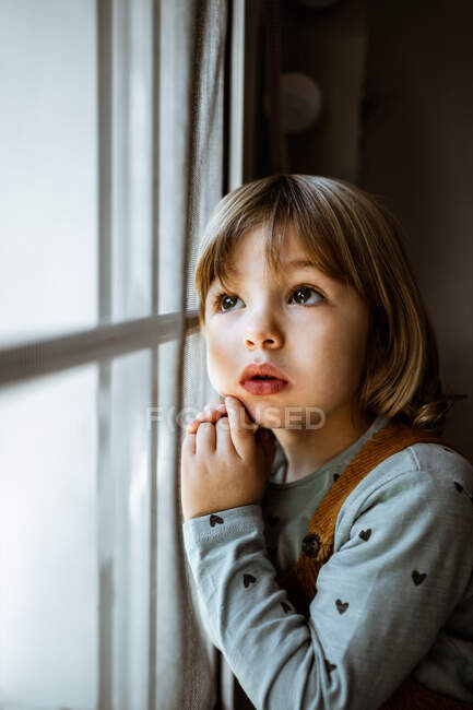 Menina adorável em roupas casuais olhando para fora da janela enquanto descansa no quarto acolhedor em casa — Fotografia de Stock