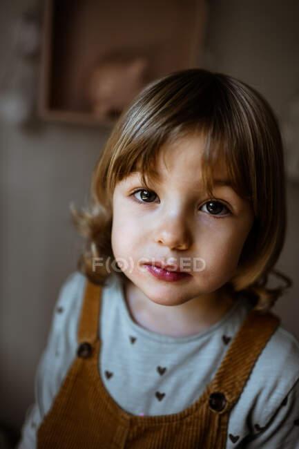 Desde arriba adorable niña en traje casual mirando a la cámara mientras está de pie sobre el fondo borroso de la acogedora habitación en casa - foto de stock