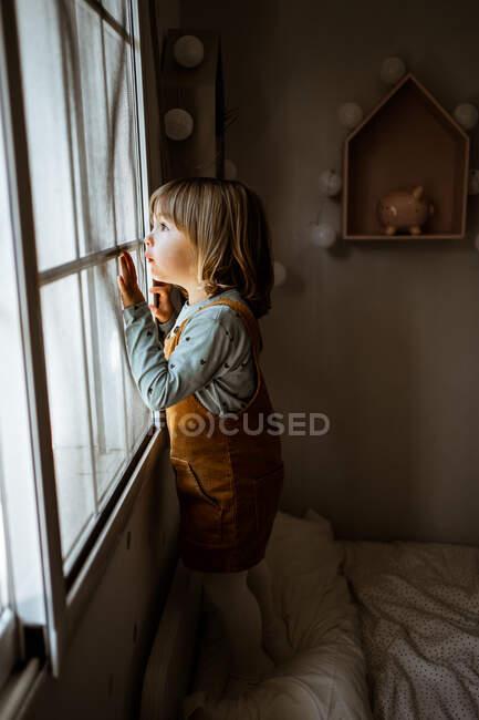 Adorabile bambina in abiti casual guardando fuori dalla finestra mentre riposava in camera accogliente a casa — Foto stock