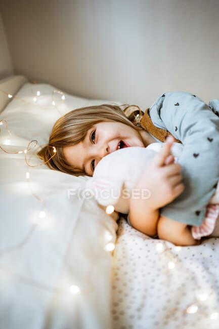 Aufgeregtes kleines Mädchen umarmt Plüschtier und lacht, während es auf weichem Bett in der Nähe von Lichterketten zu Hause liegt — Stockfoto