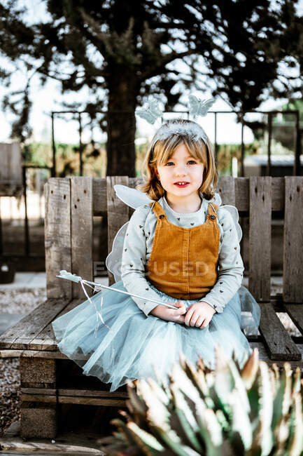 Adorable little girl in fairy costume sitting on shabby wooden bench and looking at camera while spending time in yard — Stock Photo