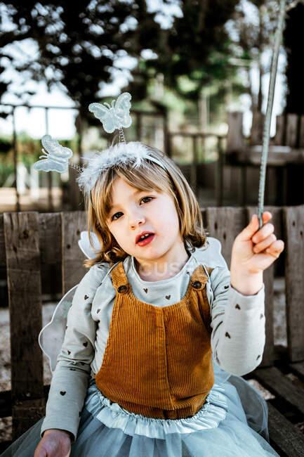 Красивая маленькая девочка в сказочном костюме сидит на потрепанной деревянной скамейке и смотрит в камеру, проводя время во дворе — стоковое фото