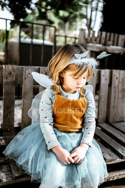 Adorable niña en traje de hadas sentada en un banco de madera y mirando a la cámara mientras pasa tiempo en el patio - foto de stock