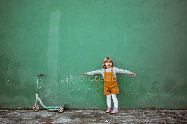 Menina com braços estendidos de pé perto de parede verde intemperado e chutar scooter e contando enquanto joga esconder e procurar — Fotografia de Stock