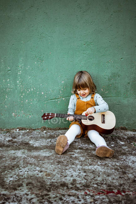 Little girl with ukulele sitting on rough ground near kick scooter against weathered green wall on street — Stock Photo