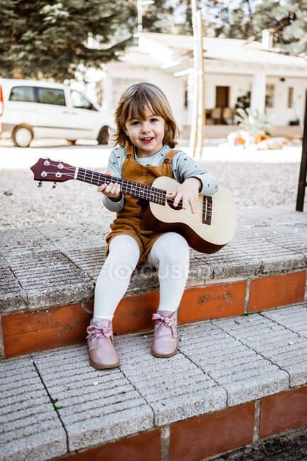 Ganzkörperfröhliches kleines Mädchen in lässiger Kleidung, das auf Stufen sitzt und auf der Vorstadtstraße Ukulele spielt und in die Kamera lächelt — Stockfoto