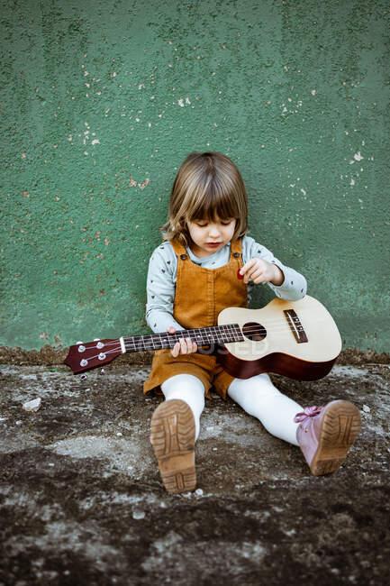 Petite fille avec ukulélé assis sur un terrain accidenté près de trottinette de coup de pied contre le mur vert altéré sur la rue — Photo de stock