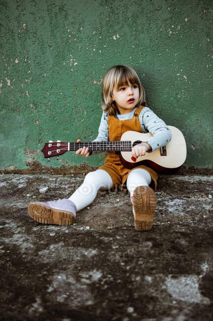 Bambina con ukulele seduta su terreno accidentato vicino al calcio scooter contro il muro verde intemperie sulla strada — Foto stock