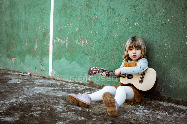 Kleines Mädchen mit Ukulele sitzt auf unwegsamem Boden neben Tretroller gegen verwitterte grüne Mauer auf der Straße — Stockfoto