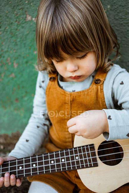 Маленька дівчинка з укулеле сидить на необжитій землі біля кидаючого скутера проти вивітрюваної зеленої стіни на вулиці. — стокове фото