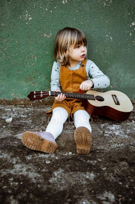 Menina com ukulele sentado em solo áspero perto de chutar scooter contra parede verde resistido na rua — Fotografia de Stock
